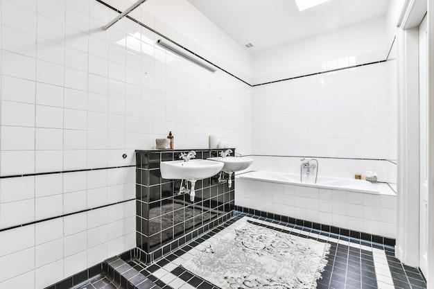 Interno lucido del bagno piastrellato con piastrelle bianche e nere con doppi lavandini e doccia aperta