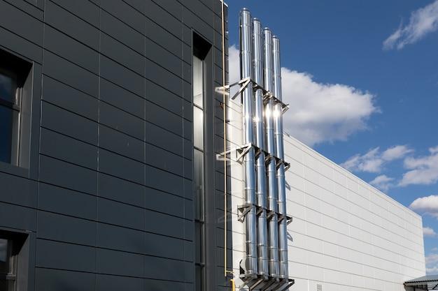 Camino in metallo lucido sulla parete esterna dell'edificio industriale su uno sfondo di cielo blu.