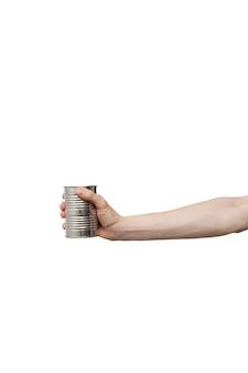 Barattolo di latta lucido del metallo tenuto a disposizione isolato su bianco. uomo che tiene cibo in scatola