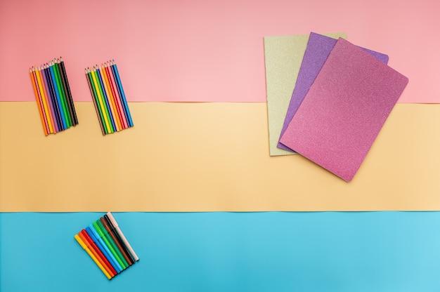 Taccuini lucidi, matite colorate e penne coloranti in un'immagine concettuale di ritorno a scuola.