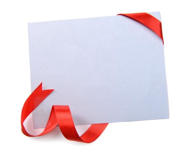Nastro rosso lucido con carta isolato su bianco