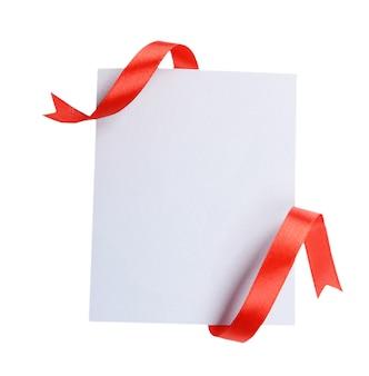 Nastro rosso brillante con carta isolato su bianco