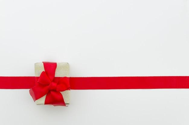 Nastro rosso lucido e scatola regalo su sfondo bianco. girato in studio. copia spazio