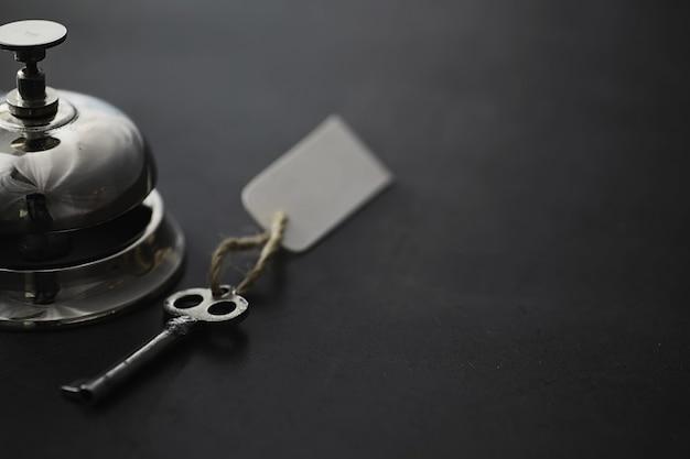 Un campanello di metallo argentato lucido alla reception dell'hotel. un tavolo in albergo presso la portineria con un campanello e la chiave della porta. chiave e campanello in un hotel.