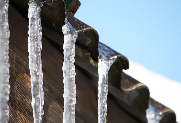 Ghiaccioli trasparenti lucidi che appendono su un tetto si chiudono.