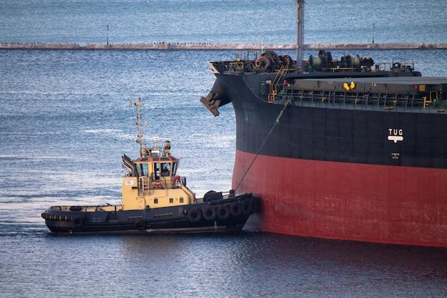 Attracco della nave in porto con assistenza al rimorchiatore su fune di ormeggio con frangiflutti sullo sfondo