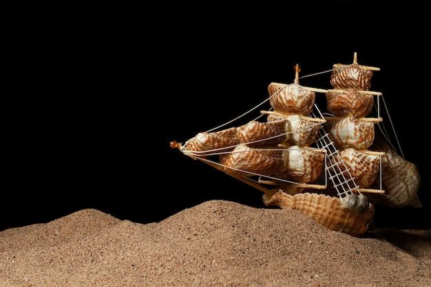 Una nave fatta di conchiglie che galleggiano sulla sabbia su uno sfondo nero