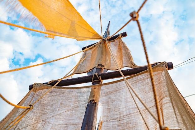 L'albero della nave con le vele beige oscilla contro un cielo blu