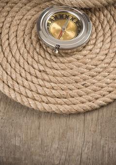 Corde e bussola della nave su fondo di legno