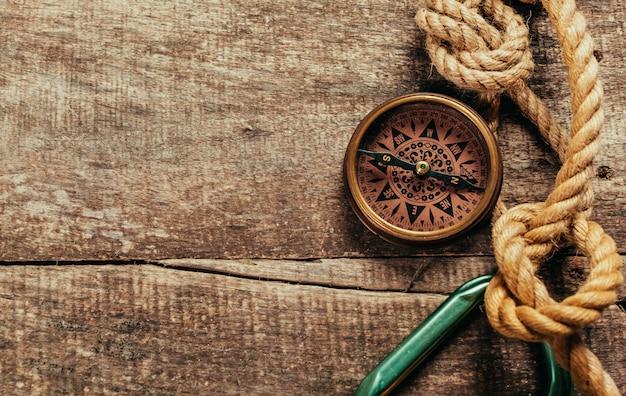 Spedica le corde e la bussola su fondo di legno