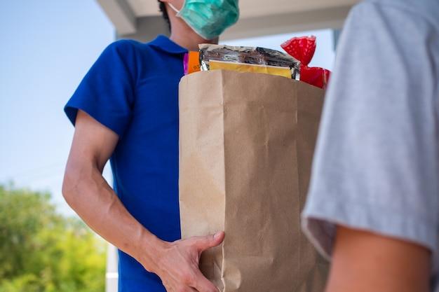 Lo spedizioniere indossa una maschera, consegna il cibo a casa dell'acquirente online. stare a casa ridurre la diffusione del virus covid-19. il mittente ha un servizio per consegnare prodotti o cibo rapidamente