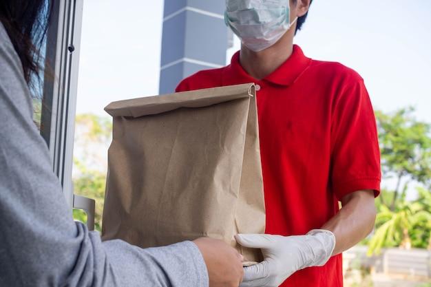 Lo spedizioniere indossa una maschera e guanti, consegna cibo a casa dell'acquirente online. stare a casa ridurre la diffusione del virus covid-19. il mittente ha un servizio per consegnare prodotti o cibo rapidamente