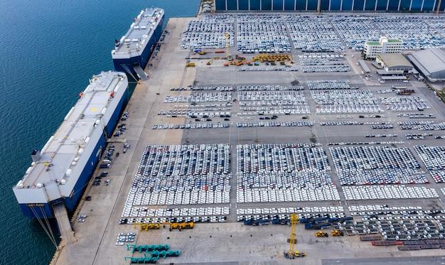 Logistica di spedizione che carica una nuova linea di produzione di auto importazione esportazione internazionale vista aerea del mare aperto