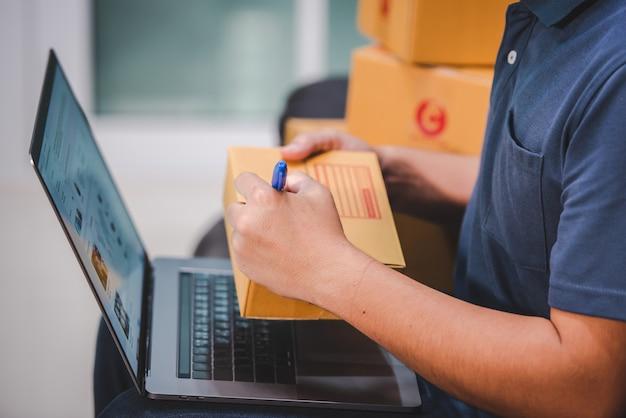 Spedizione online shopping i proprietari di piccole imprese scrivono su scatole di cartone al lavoro per le piccole e medie imprese impatto della crisi covid-19 attività di vendita online