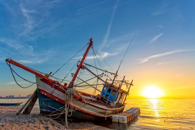 Un naufragio abbandonato sulla spiaggia e la luce del sole durante il tramonto al tramonto