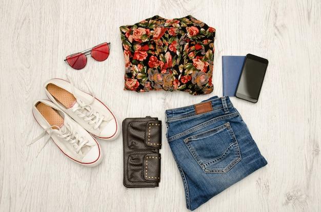 Camicia in fiori, occhiali, scarpe da ginnastica, jeans, telefono e passaporto.