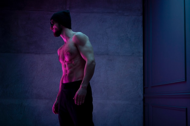 Uomo atletico senza camicia che posa con fiducia