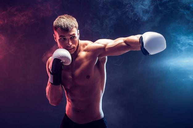 Boxer torso nudo con guanti su sfondo scuro. isolato