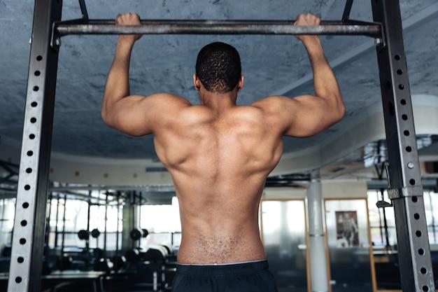 Fitness afroamericano senza camicia che fa esercizi per lo stomaco su una barra orizzontale in palestra
