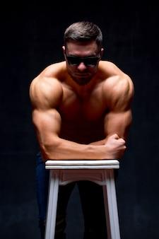 Bel maschio senza camicia con un corpo muscoloso perfetto in posa mentre si appoggia su una sedia