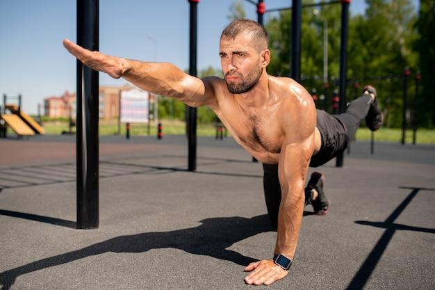 Ragazzo muscoloso torso nudo in leggins e scarpe da ginnastica che praticano esercizi di yoga sul campo sportivo il giorno di estate pieno di sole