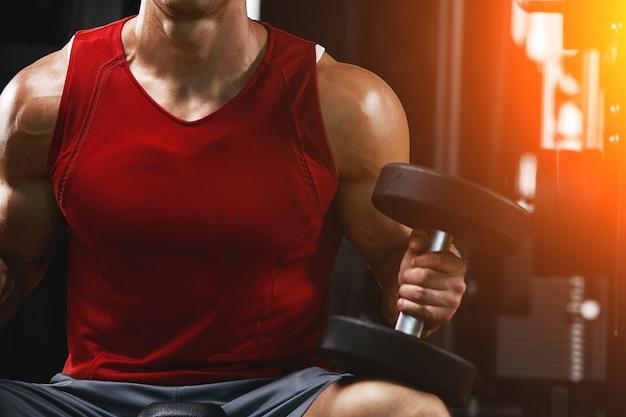 Un uomo muscoloso senza camicia sta facendo esercizi per bicipiti con esercizi con manubri come parte del suo allenamento di bodybuilding