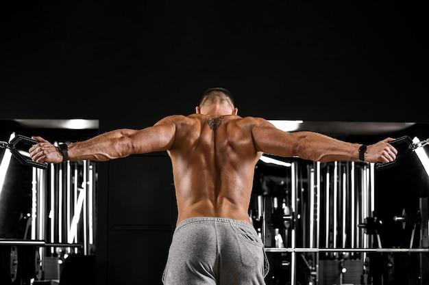 Un uomo muscoloso senza camicia sta facendo esercizi per bicipiti con esercizi con manubri