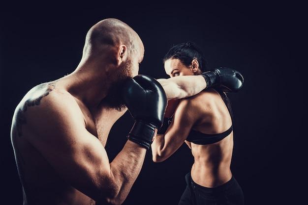Donna senza camicia che si esercita con l'allenatore alla lezione di boxe e autodifesa, studio, spazio buio