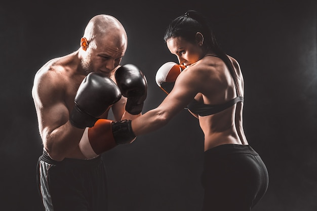 Donna senza camicia che si esercita con il trainer alla lezione di boxe e autodifesa, studio, fumo nello spazio