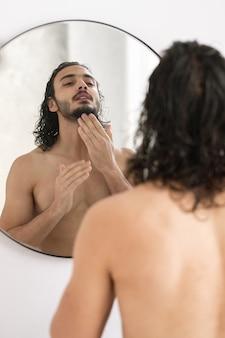 Giovane senza camicia che guarda la sua barba nello specchio mentre va a radersi dopo aver fatto il bagno al mattino