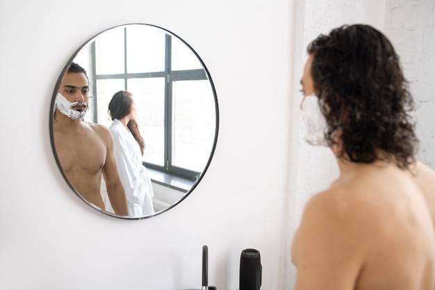 Giovane senza camicia con schiuma da barba sulla barba in piedi davanti allo specchio con la riflessione og la sua ragazza che indossa accappatoio bianco