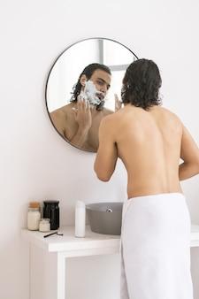 Giovane senza camicia con un asciugamano bianco sui fianchi che applica schiuma da barba sulla sua barba davanti allo specchio in bagno