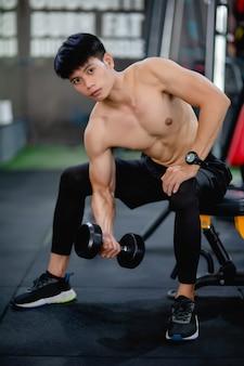 Giovane muscolare senza camicia con manubri per esercizio, allenamento di sollevamento in palestra,