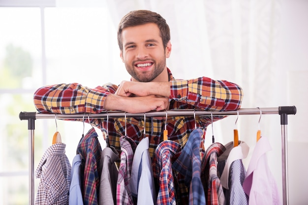 Camicie tutti i giorni. bel giovane appoggiato all'armadio con diverse camicie e sorridente