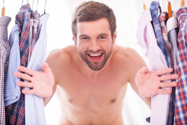 Camicie tutti i giorni. felice giovane uomo a torso nudo che guarda attraverso varie camicie appese alle grucce e sorride