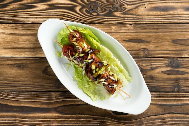 Shish kebab di pollo e zucchine in salsa teriyaki con foglie di lattuga e cipolle verdi in un bel piatto di ceramica sul tavolo della cucina in legno.