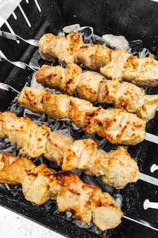 I pezzi di carne di shish kebab vengono fritti su spiedini. marinata al curry.