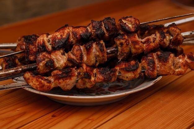 Shish kebab su un piatto su un tavolo di legno. shashlik.