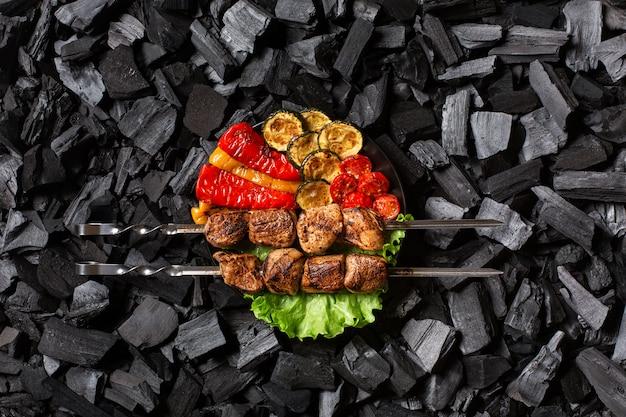 Shish kebab su spiedini e peperoni grigliati, zucchine, ciliegia, pomodoro su un piatto rotondo.