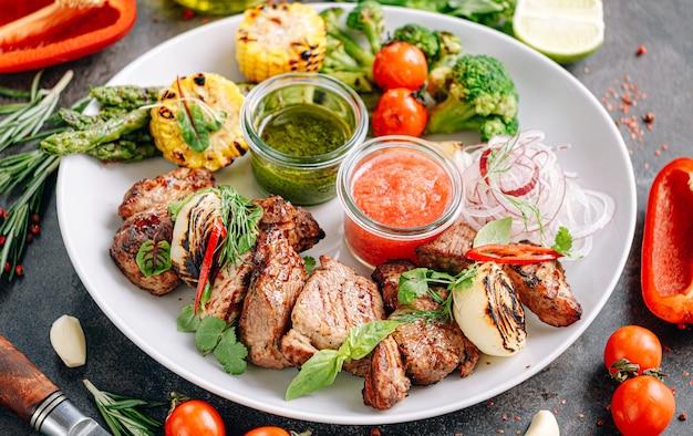 Shish kebab e verdure grigliate e servite su un piatto bianco.