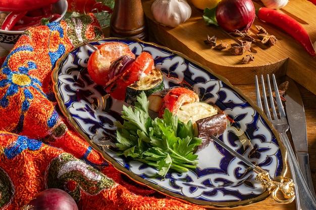 Shish kebab di verdure in un piatto con un tradizionale ornamento uzbeko. melanzane, zucchine, pomodori e cipolle fritte su uno spiedino.