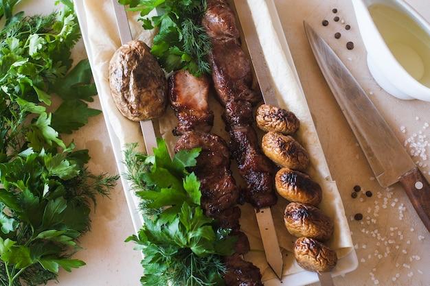 Shish-kebab con verdure grigliate sul piatto bianco.