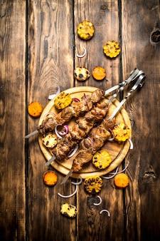 Shish kebab con verdure grigliate. sullo sfondo di legno.