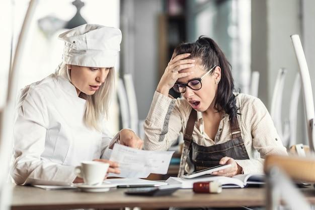Shock per la contabilità della chef donna e proprietaria del ristorante, seduta su scartoffie.