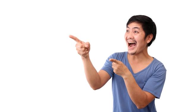 Scossa e sorpresa faccia dell'uomo asiatico che punta il dito sullo spazio vuoto.