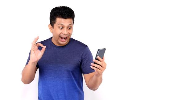 Shock e faccia sorpresa dell'uomo asiatico che presenta smart phone su bianco