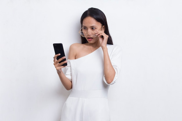 Shock giovane bella donna asiatica utilizzando il telefono cellulare isolato su sfondo bianco