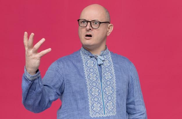 Uomo slavo adulto scioccato in camicia blu che indossa occhiali ottici tenendo la mano aperta e guardando di lato