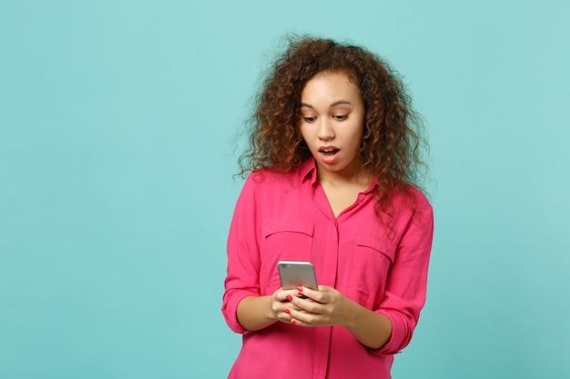 Ragazza africana scioccata in abiti casual rosa utilizzando il telefono cellulare digitando un messaggio sms isolato su sfondo blu turchese parete in studio. persone sincere emozioni, concetto di stile di vita. mock up copia spazio.
