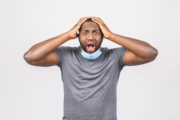 Uomo afroamericano stupito scioccato con mascherina medica con grandi occhi e braccia alzate Foto Premium